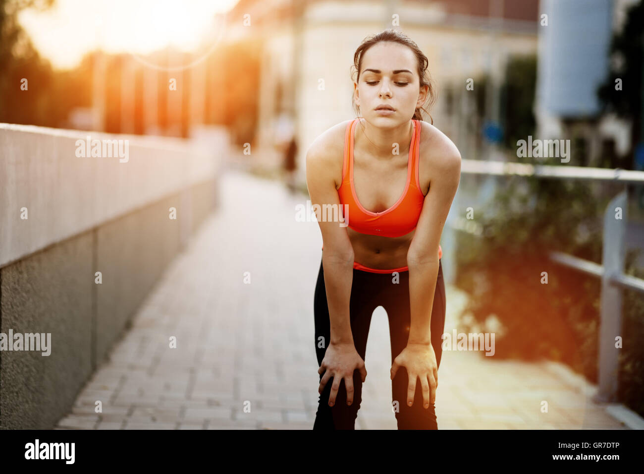 Tired female jogger resting after finishing run - Stock Image