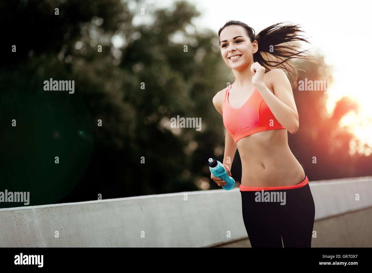 Happy sporty female jogger smiling - Stock Image