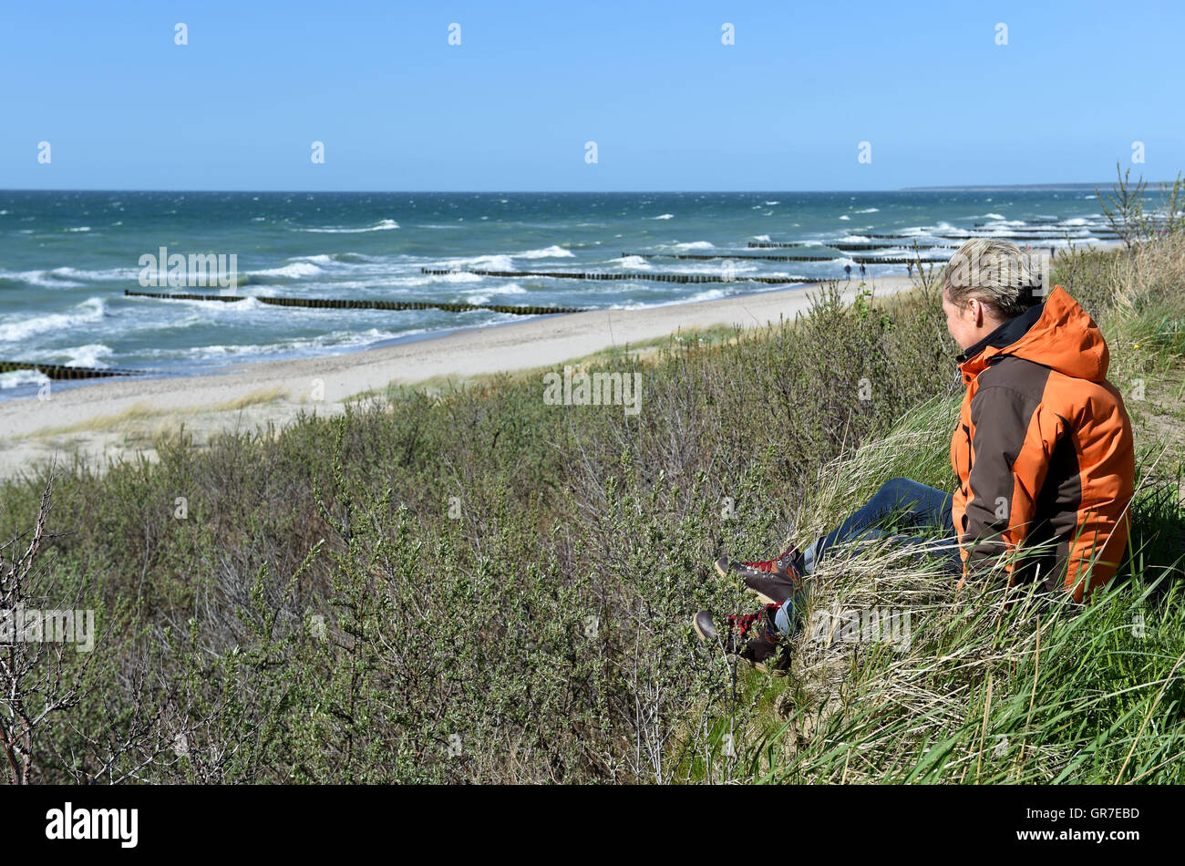 Woman Sitting By The Sea - Stock Image