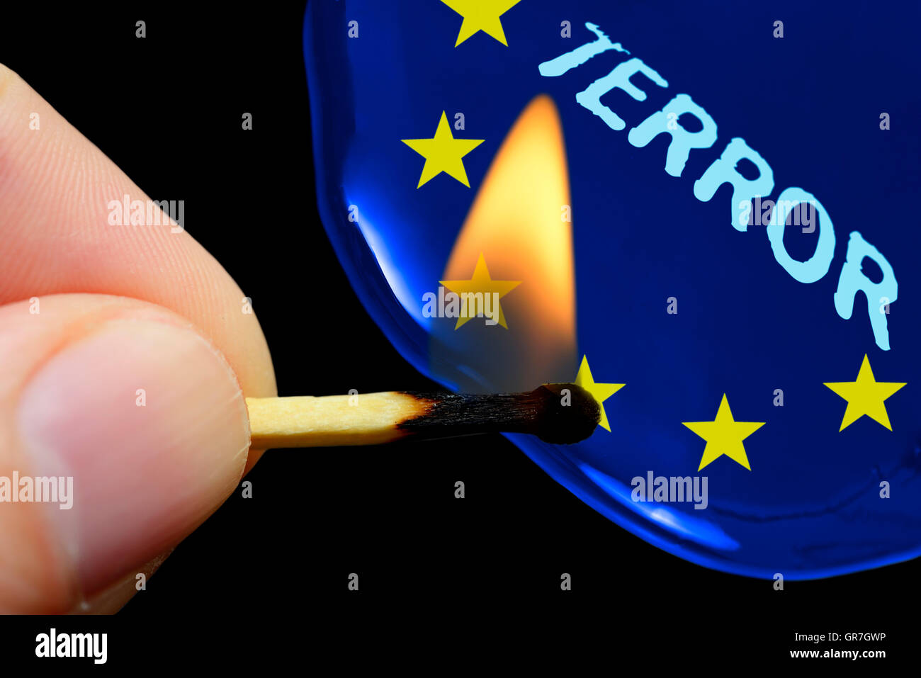 Finger Holding Burning Match In Front Of Flag Of Europe, Terror Threats - Stock Image