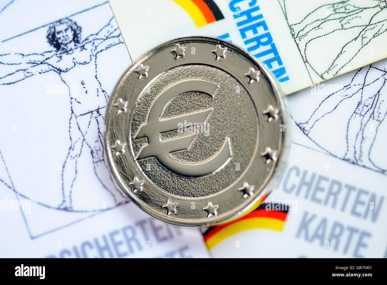 Euro Sign On Coin And Health Insurance Cards - Stock Image