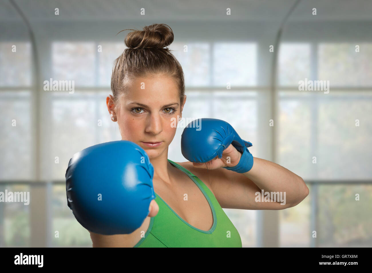 Young Woman With Boxing Gloves Showing Ready For Battle - Stock Image