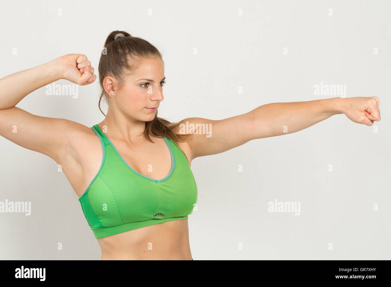 Woman In Green Bustier Shows Ready For Battle - Stock Image