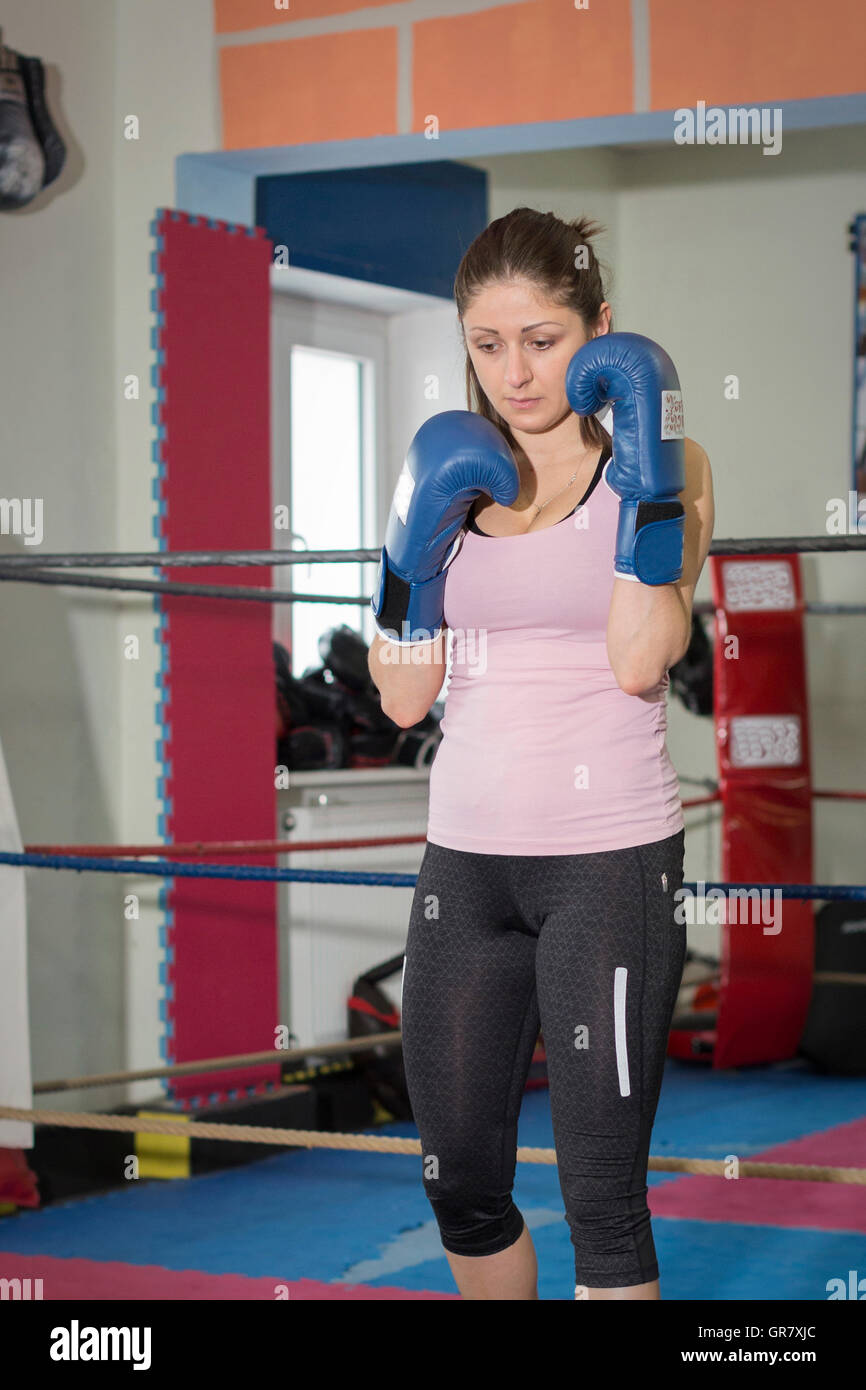 Young Woman Training Boxing And Tries To Protect Her Face With His Fists - Stock Image