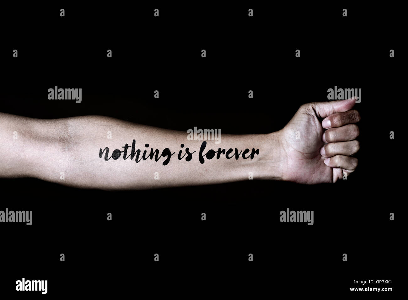 closeup of a young caucasian man with the text nothing is forever simulating a tattoo in his forearm, against a - Stock Image