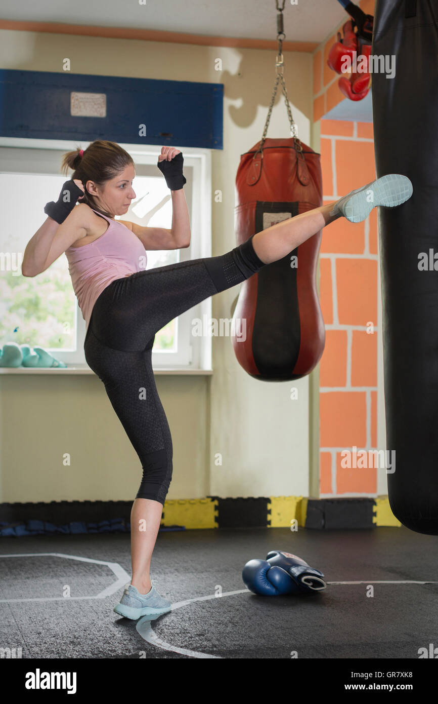 Young Woman Exercising Her Punching Power With The Help Of A Punching Bag - Stock Image