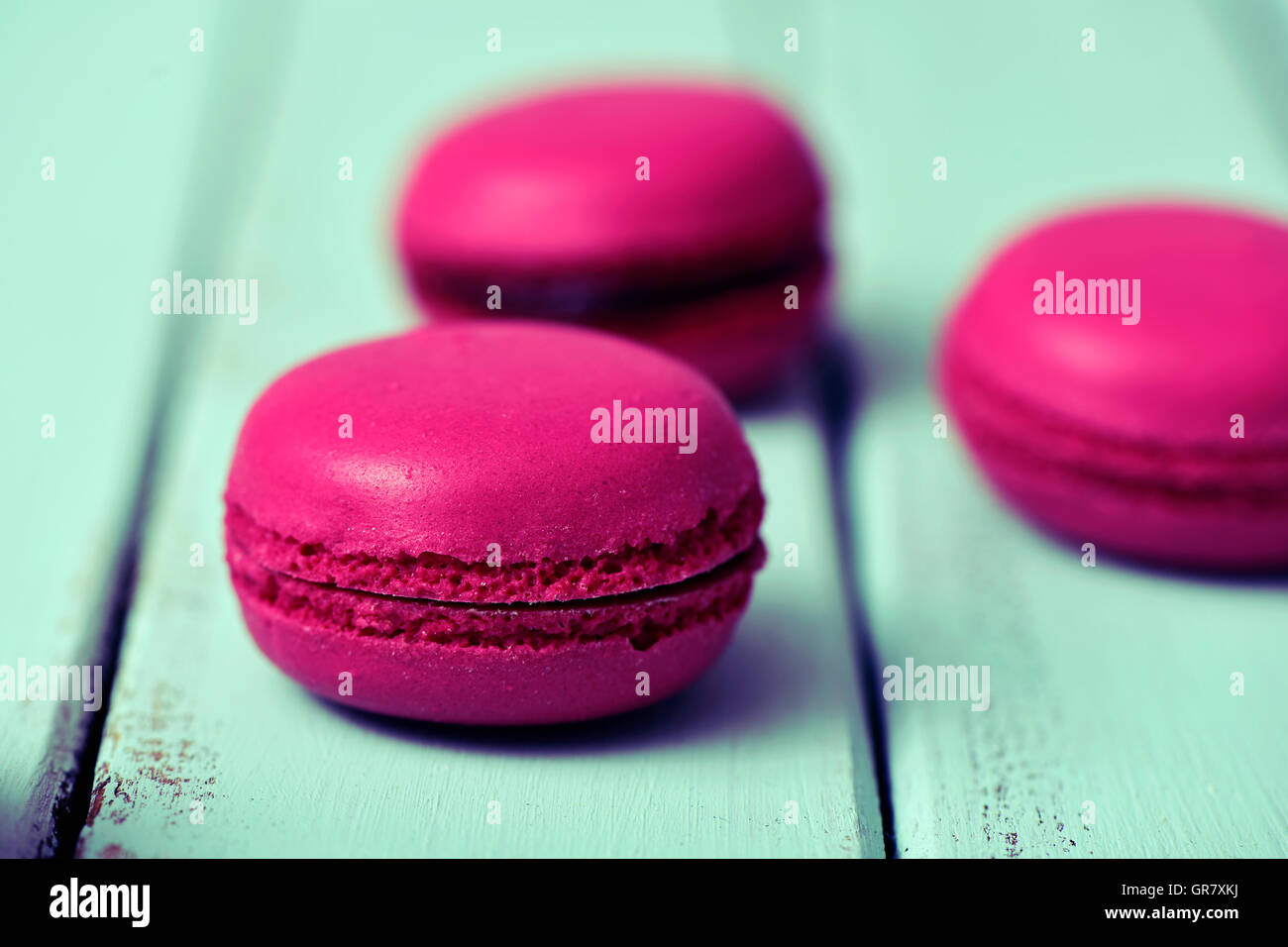 closeup of some appetizing purple macarons on a pale blue rustic wooden surface - Stock Image