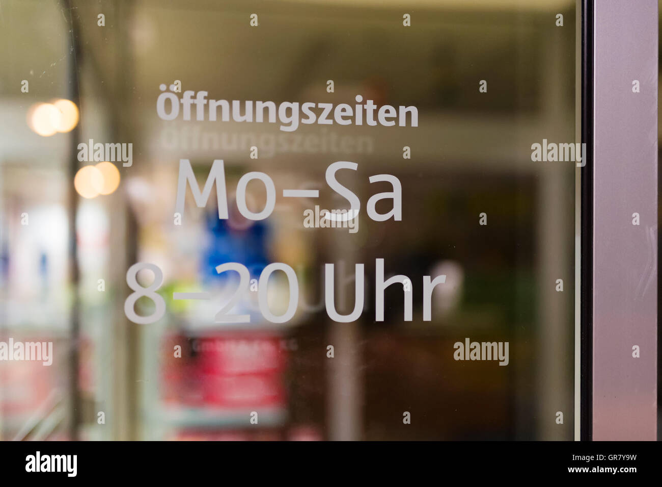With The Opening Times Labeled Glass Door Of A Shop. - Stock Image