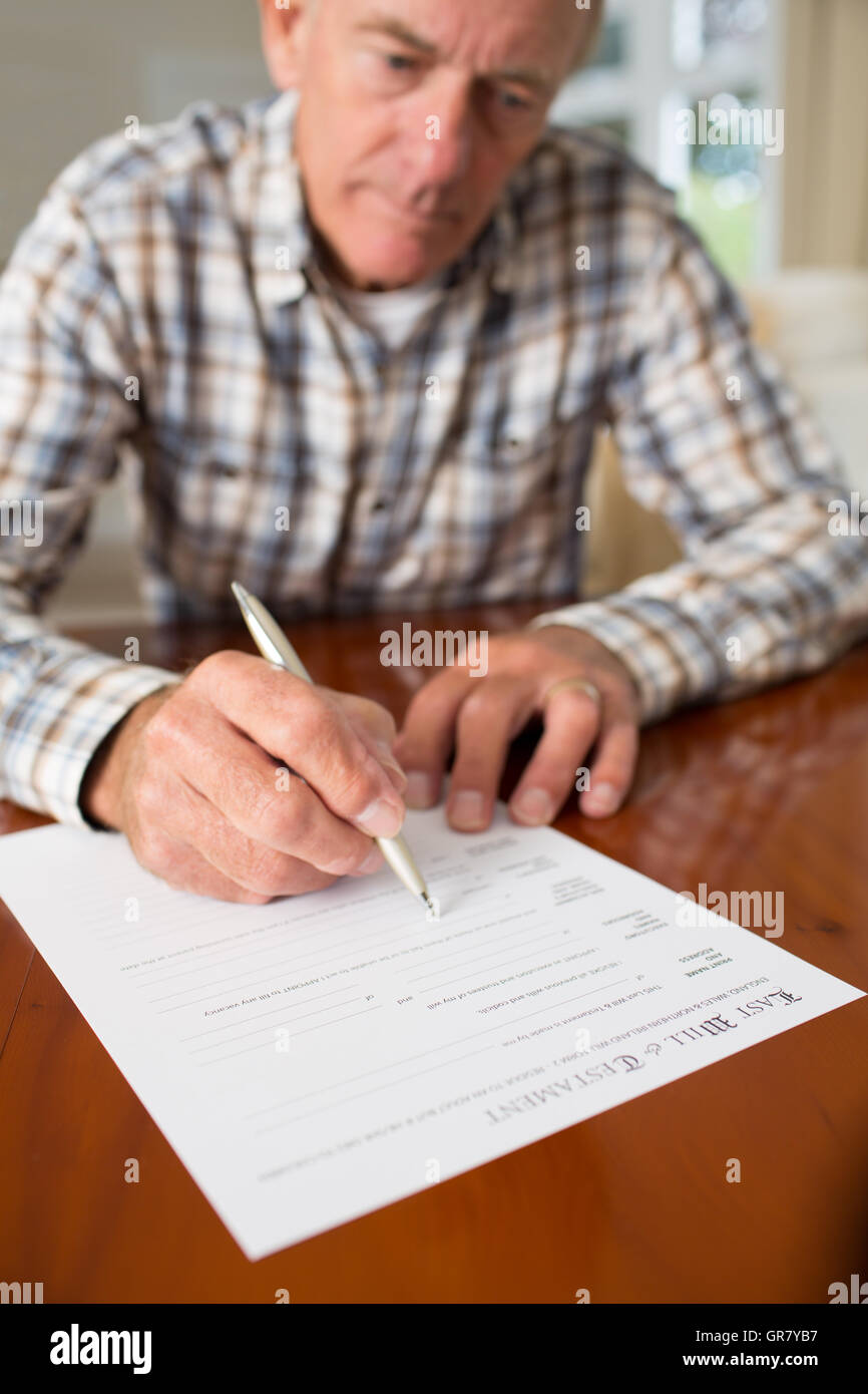 Senior Man Signing Last Will And Testament At Home - Stock Image