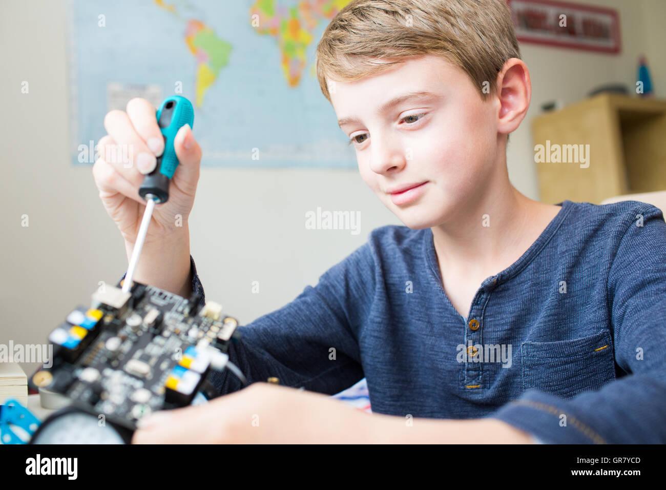 Boy Assembling Robotic Kit In Bedroom - Stock Image