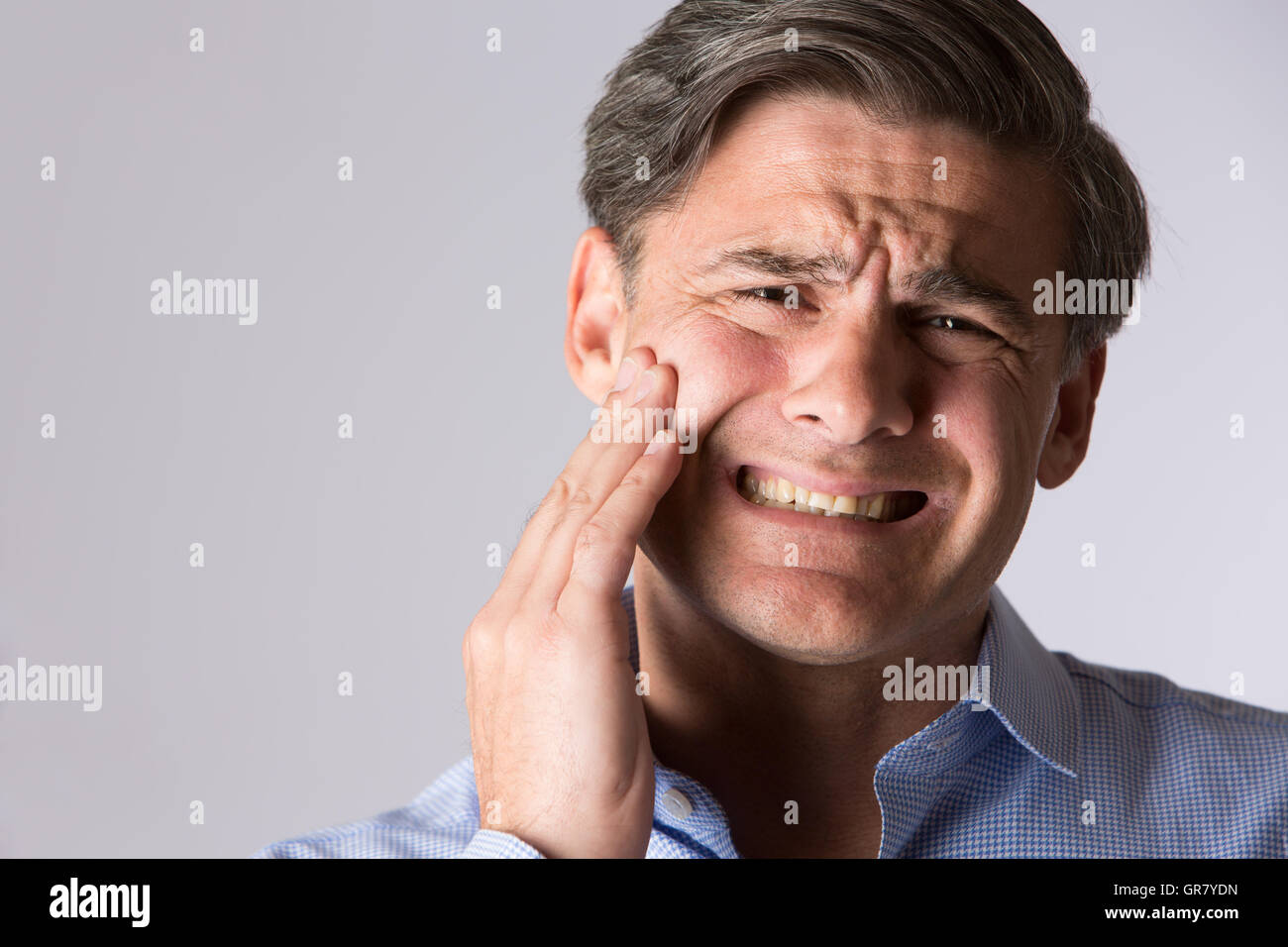 Studio Portrait Of Man Suffering With Toothache - Stock Image