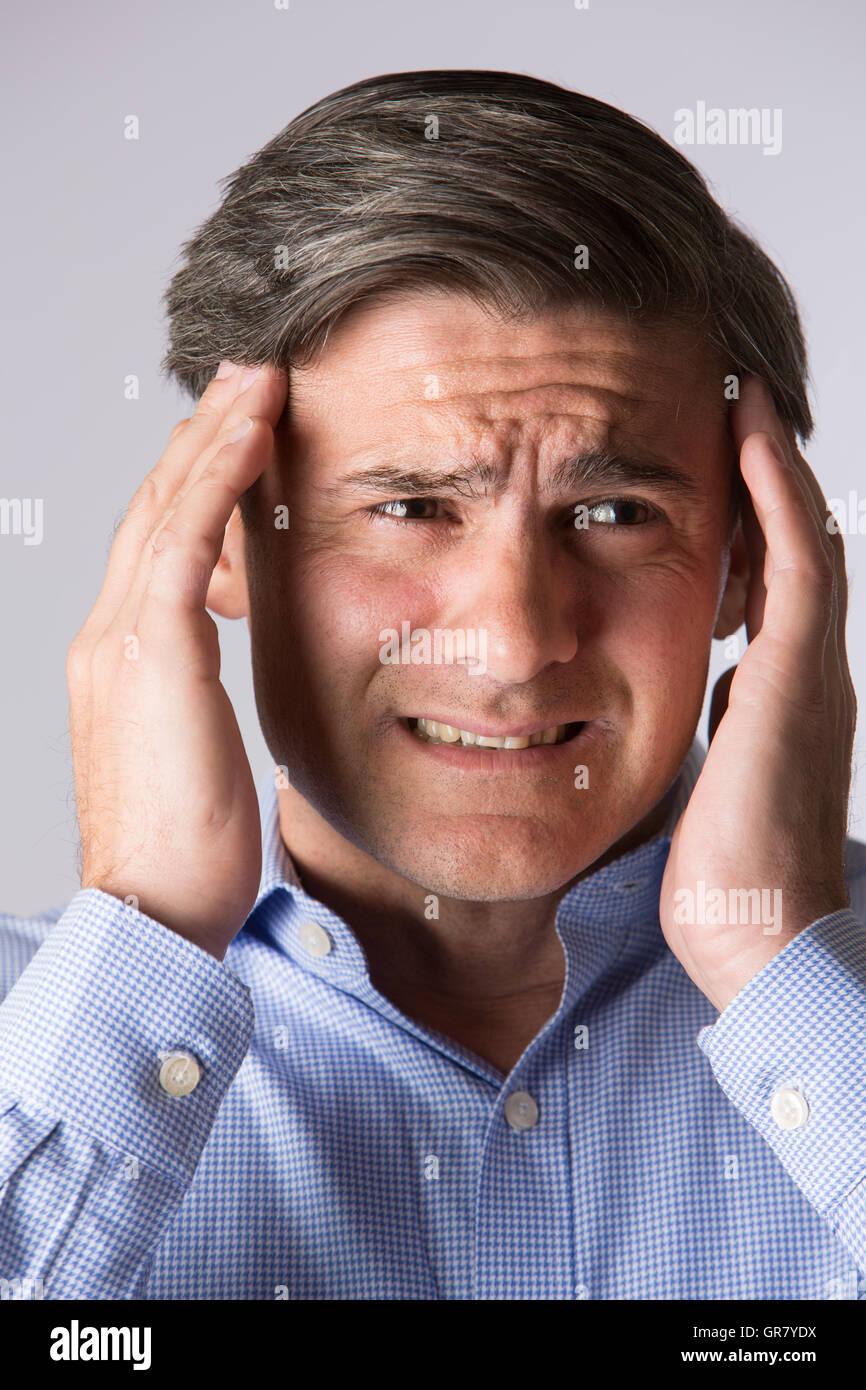 Studio Portrait Of Man Suffering With Headache - Stock Image
