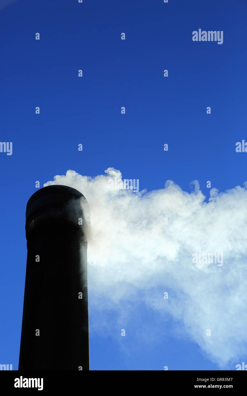 Smoke pours out of a chimney under a vibrant clear blue sky. CO2 emissions are high on current concerns regarding - Stock Image