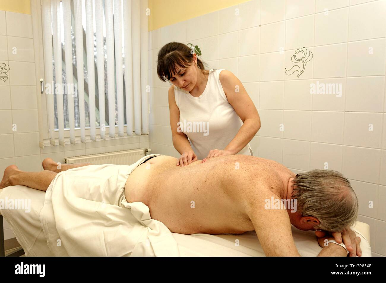 Vibration, Muscle Tremors Is From Therapist To Seniors Back Generated At The Spa Cegled - Stock Image