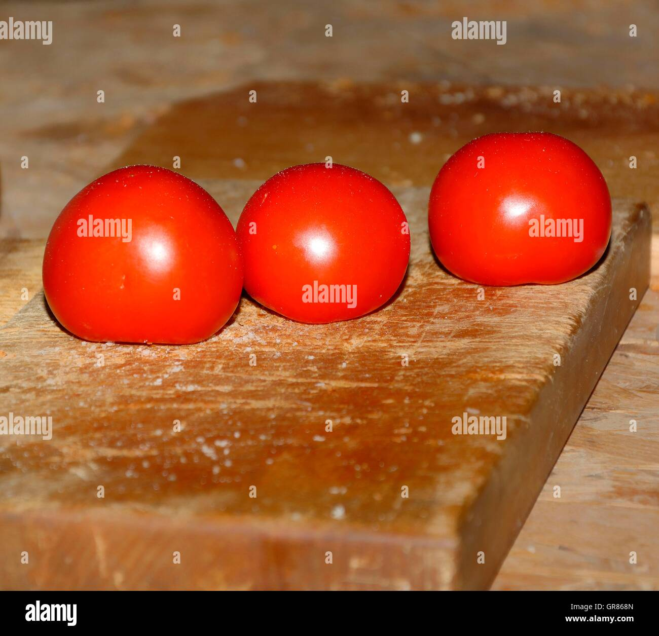 Three Tomatoes, Solanum Lycopersicum, On A Cutting Board With Salzbroeseln - Stock Image