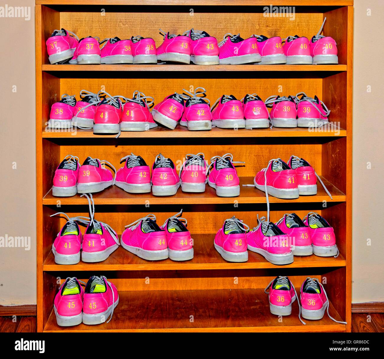 Magenta Bowling Shoes In Wooden Shoe Rack - Stock Image