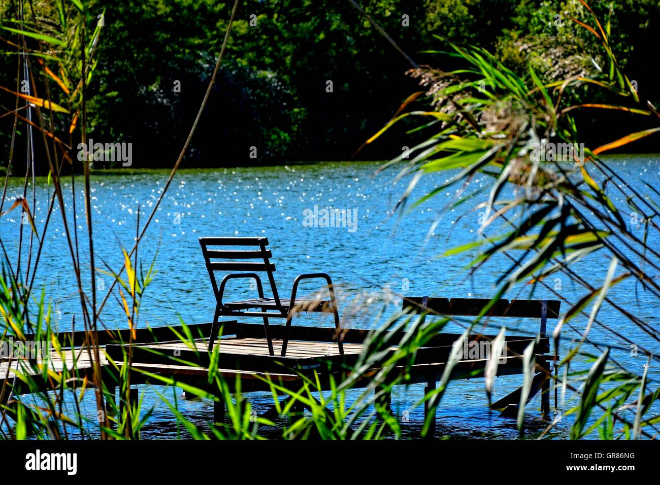 Fishing Pier With Chair And Fishing Waters - Stock Image