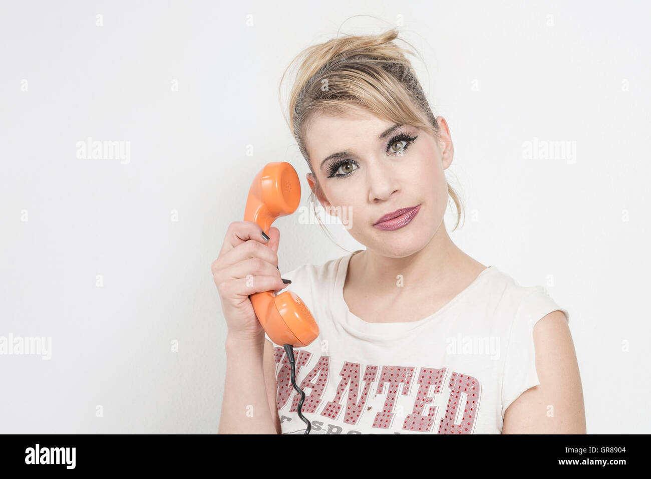 Young Blond Woman With Thoughtful And Naive Look During A Telephone Conversation - Stock Image