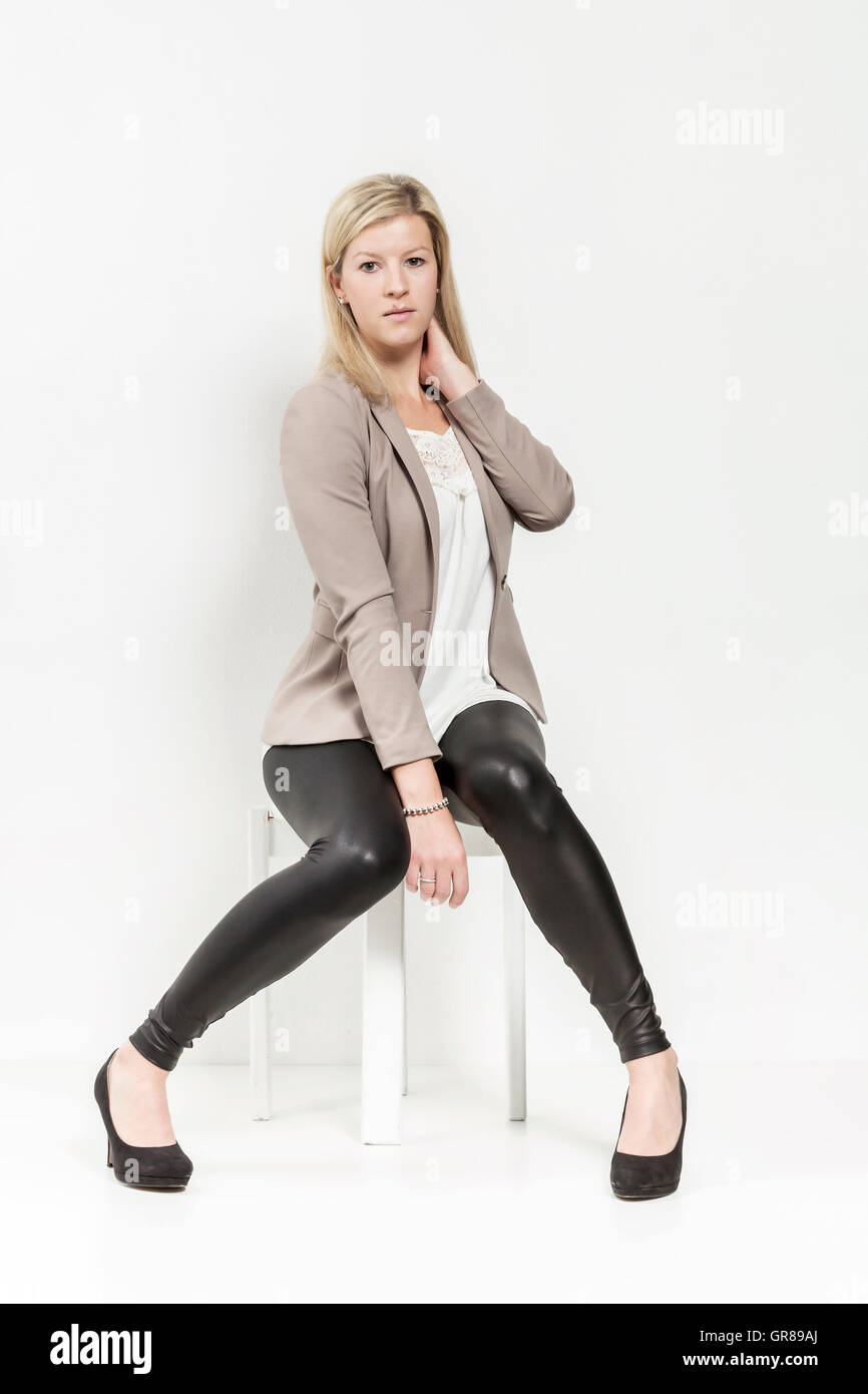Young Woman With Long Blond Hair Posing In Black Shiny Leggings And Blazer Against White Background - Stock Image