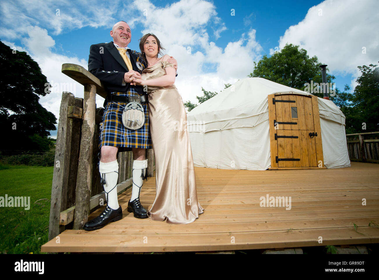 A couple just married in Ireland stand outside a yurt - Stock Image