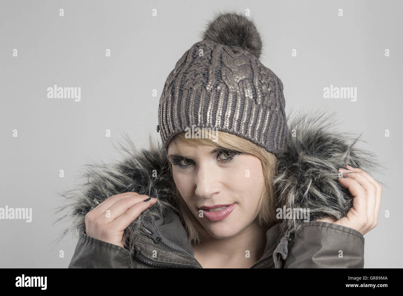 Portrait Shot Of A Young Woman With Blond Hair And Knitted Hat - Stock Image
