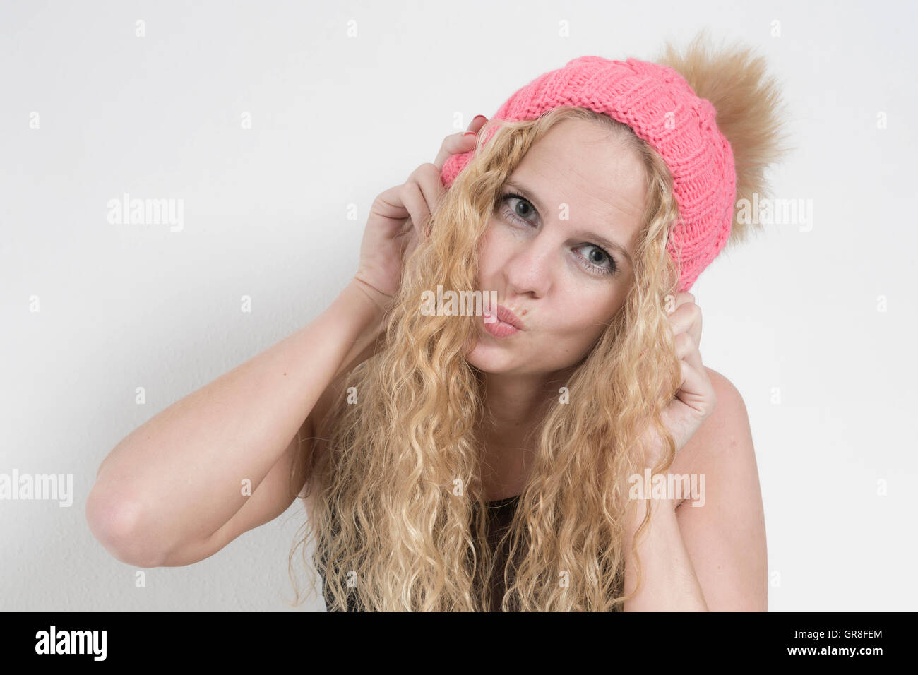 Portrait Shot Of A Young Woman With Long Blond Hair And Knit Cap, The Grimaces Cuts - Stock Image
