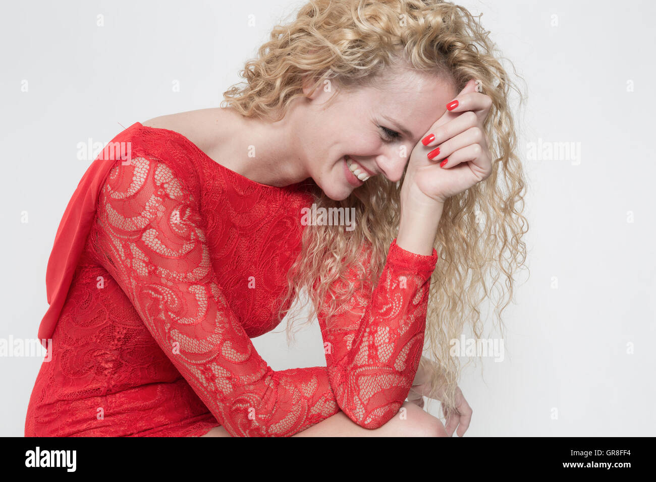Hearty Laugh Of A Pretty Young Woman In Red Cocktail Dress - Stock Image
