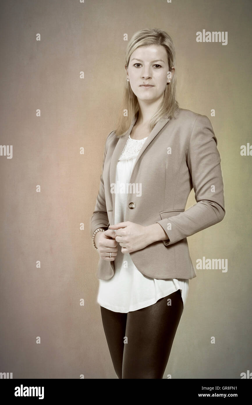 Young Woman With Long Blond Hair Posing In Black Shiny Leggings And Blazer Before Beige Background Stock Photo