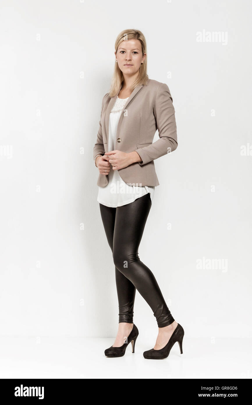 Young Woman With Long Blond Hair Posing In Black Shiny Leggings And Blazer Before Beige Background - Stock Image