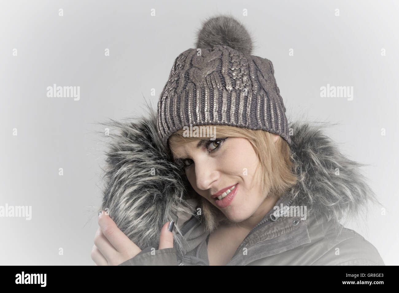 Portrait Shot Of A Young Woman With Long Blond Hair And Knit Cap - Stock Image