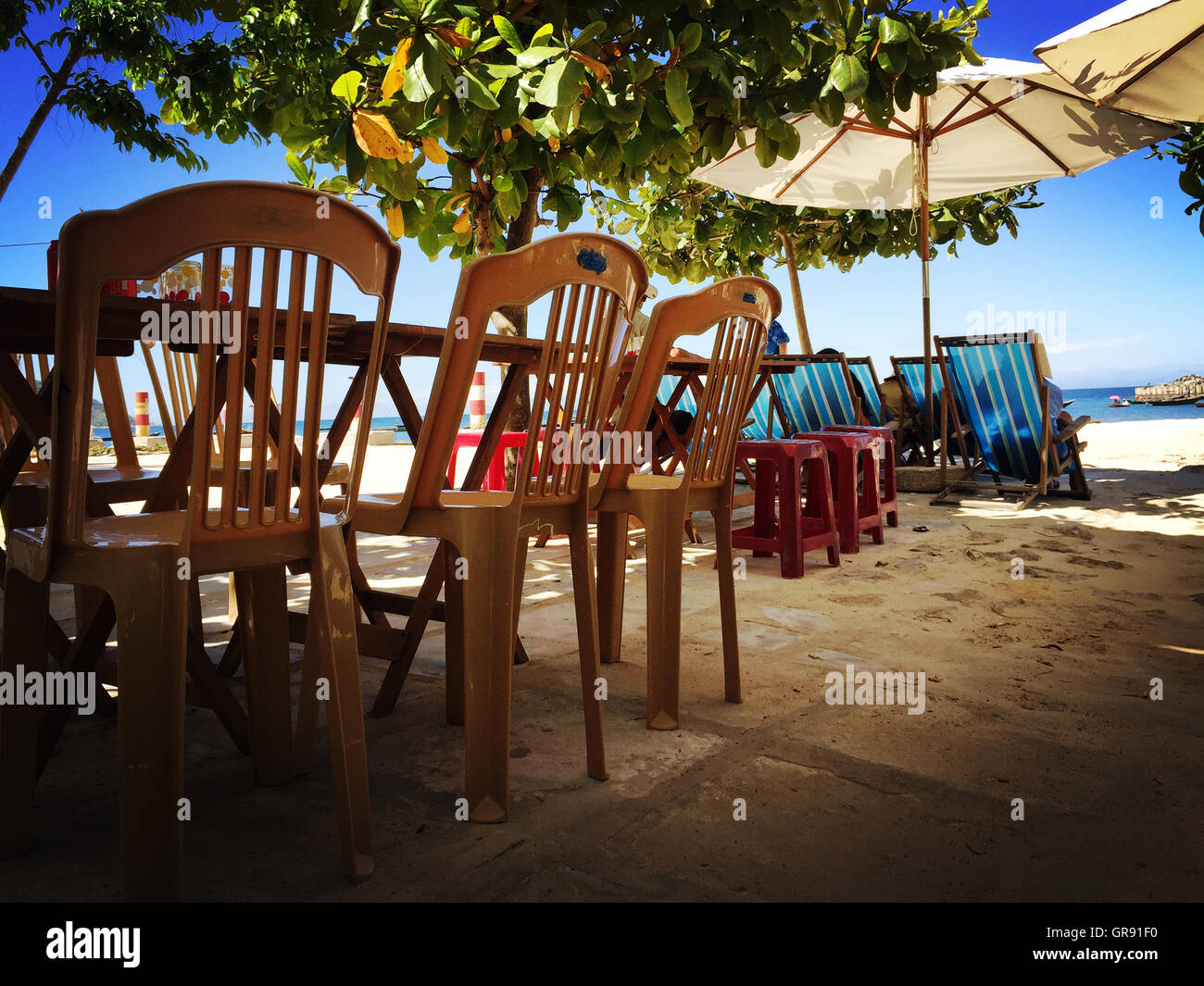 Tables And Chairs Besides Parasols On Beach - Stock Image