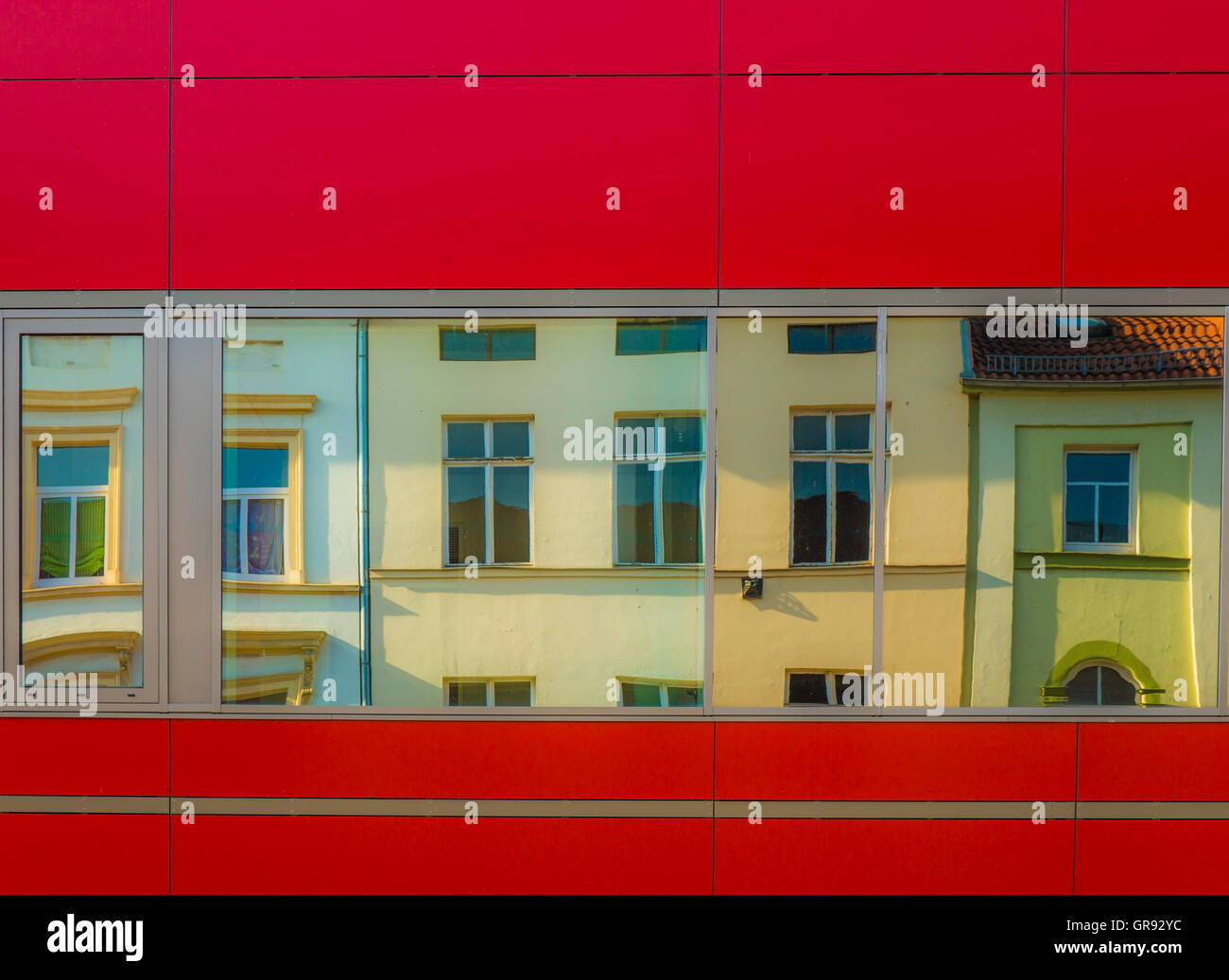 Modern Red Facade With Reflection Of Old Houses In The Windows - Stock Image