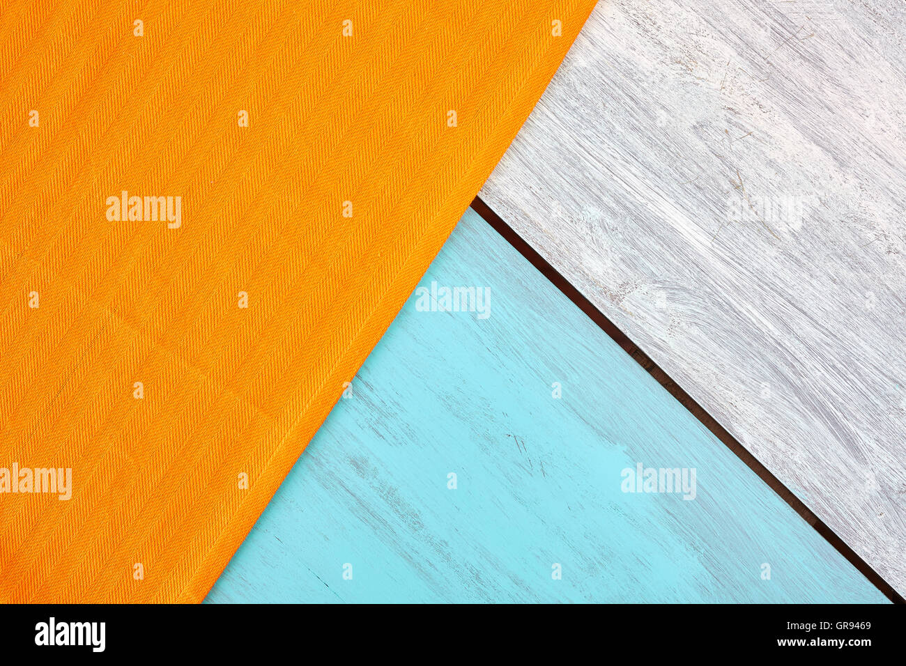 Rustic blue and white painted wooden table with a orange tablecloth, view from above, copy space. - Stock Image