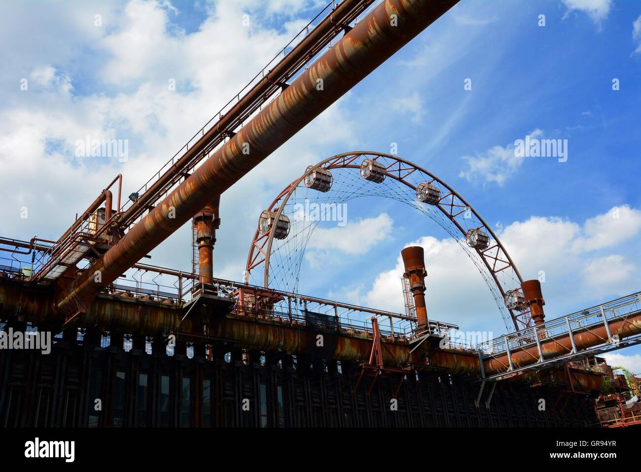 Low Angle View Of Rusty Industry Against Cloudy Sky At Zollverein Coal Mine Industrial Complex - Stock Image