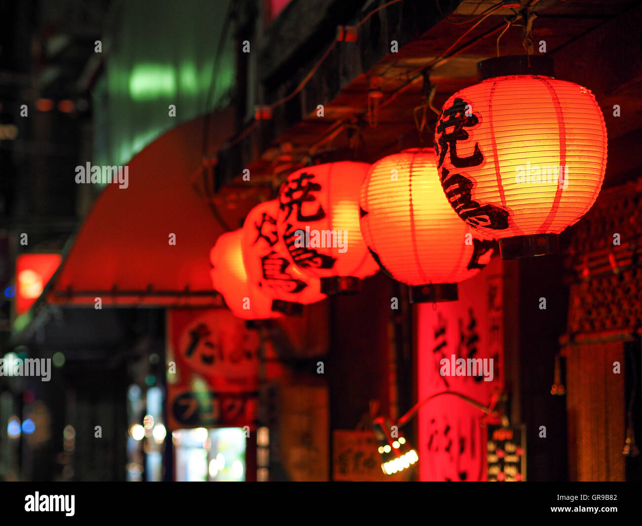 Red Illuminated Chinese Lanterns Hanging Outside Shop At Night - Stock Image