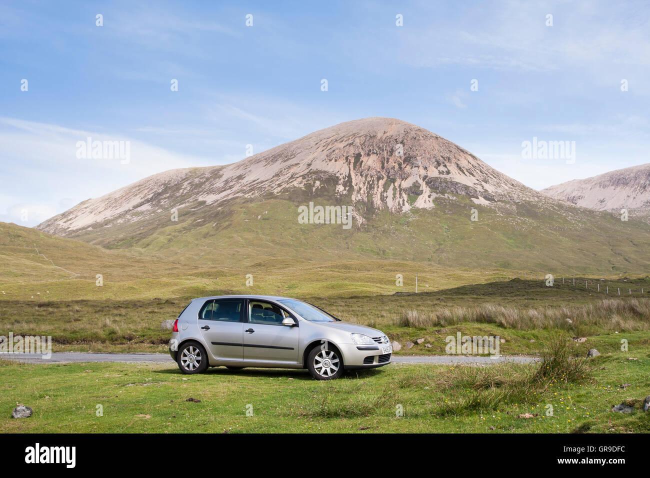 Volkswagen Golf car parked next to road with Beinn Dearg behind, Strathaird, Isle of Skye, Scotland, United Kingdom - Stock Image