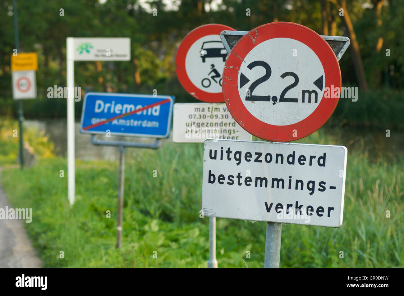 Many road signs along a small road - Stock Image