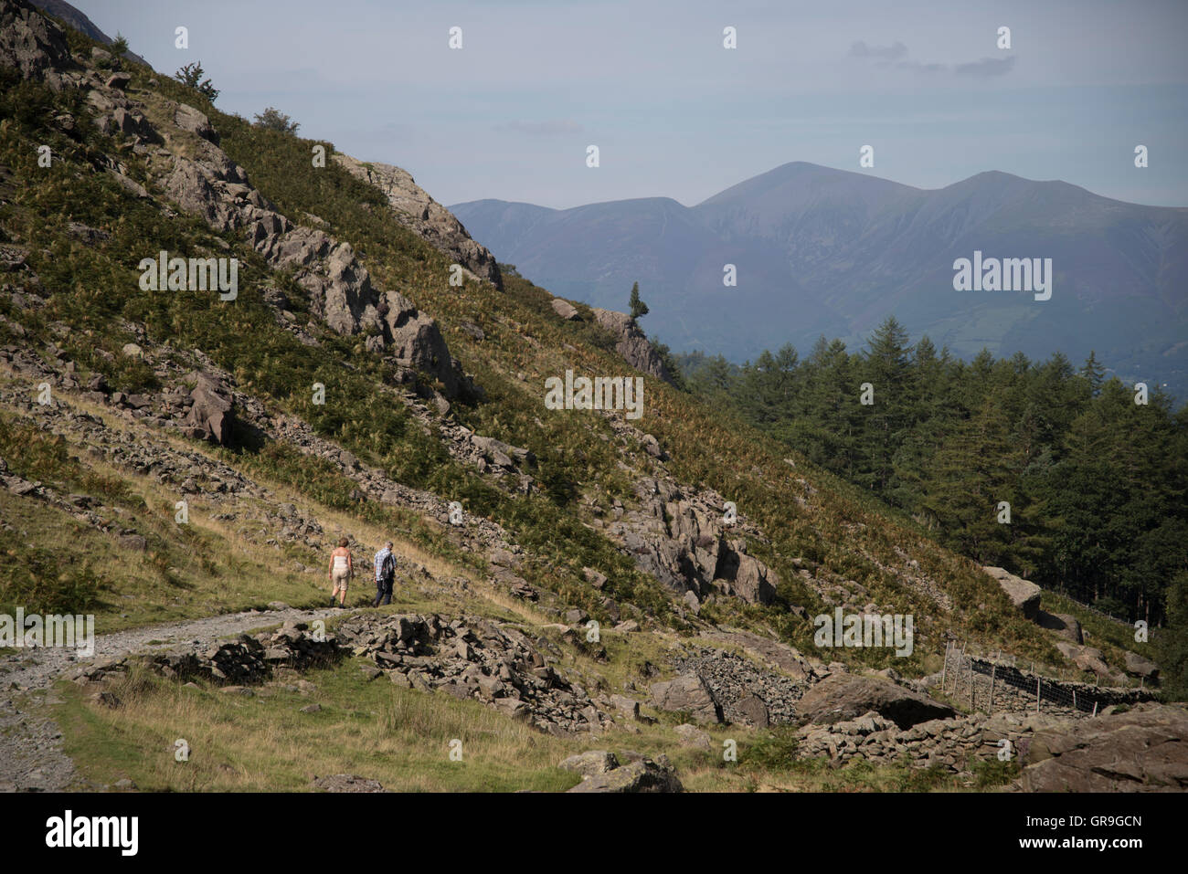 Walkers descend from Castle Crag , North Western Fells, Lake District, Cumbria, United Kingdom - Stock Image
