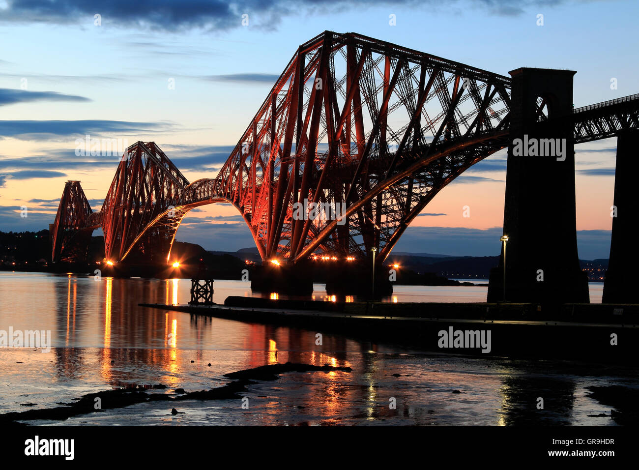 The Forth Bridge illuminated at night, South Queensferry, Lothian, Scotland, UK - Stock Image