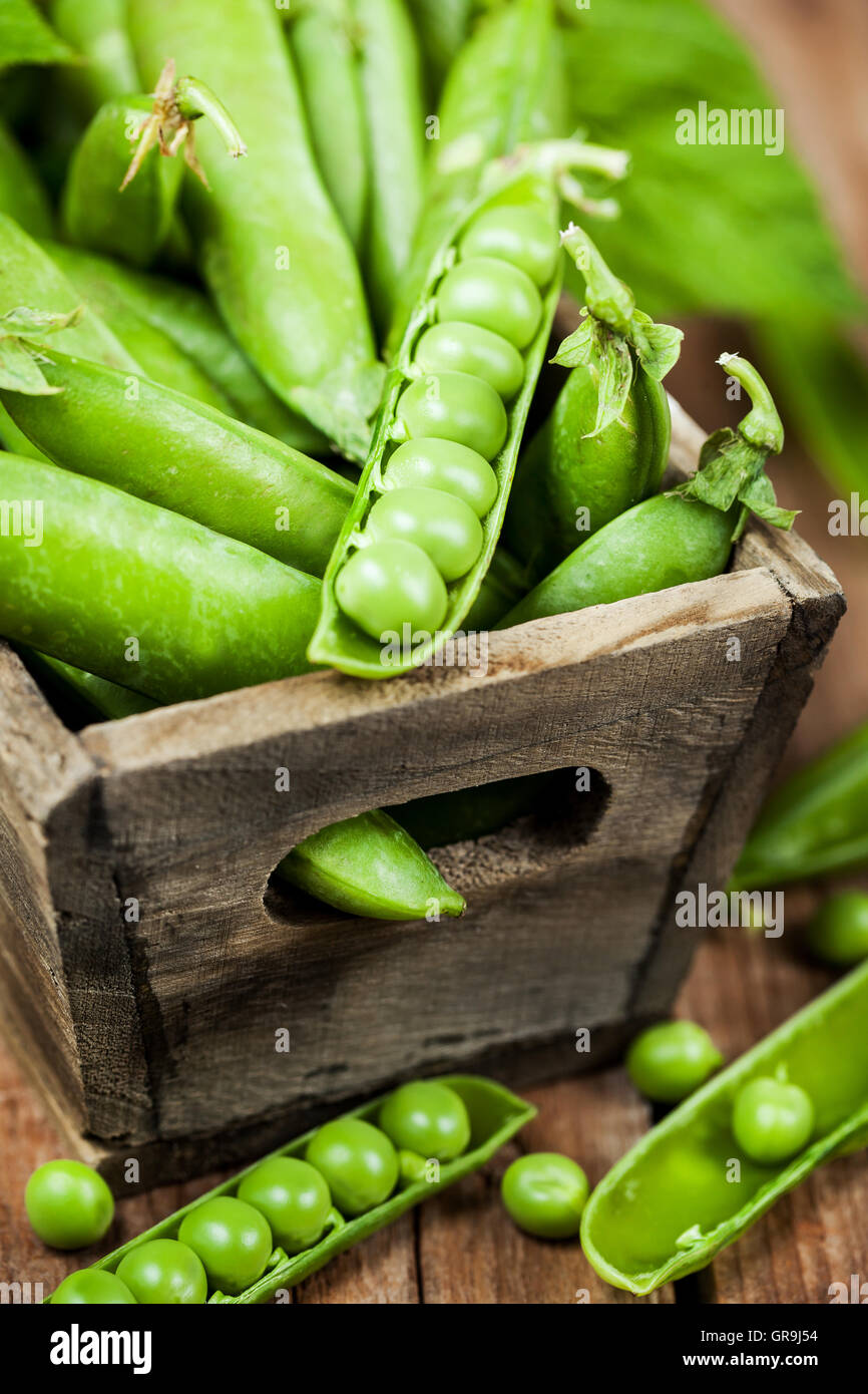 Fresh ripe green peas in wooden box - Stock Image