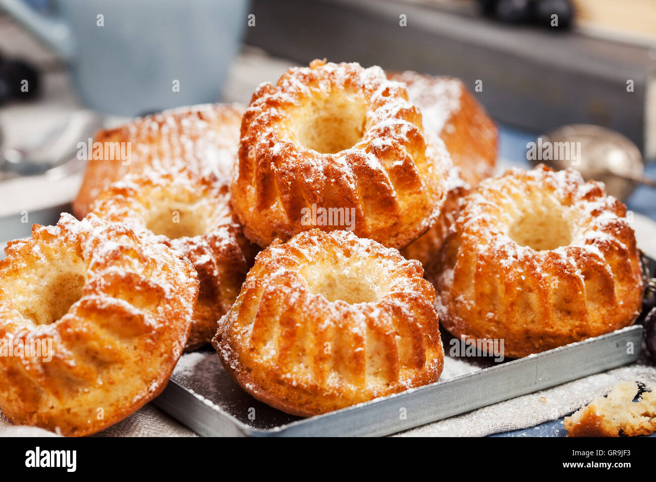 Fresh homemade delicious mini bundt cakes (muffins) and cup of coffee on background Stock Photo