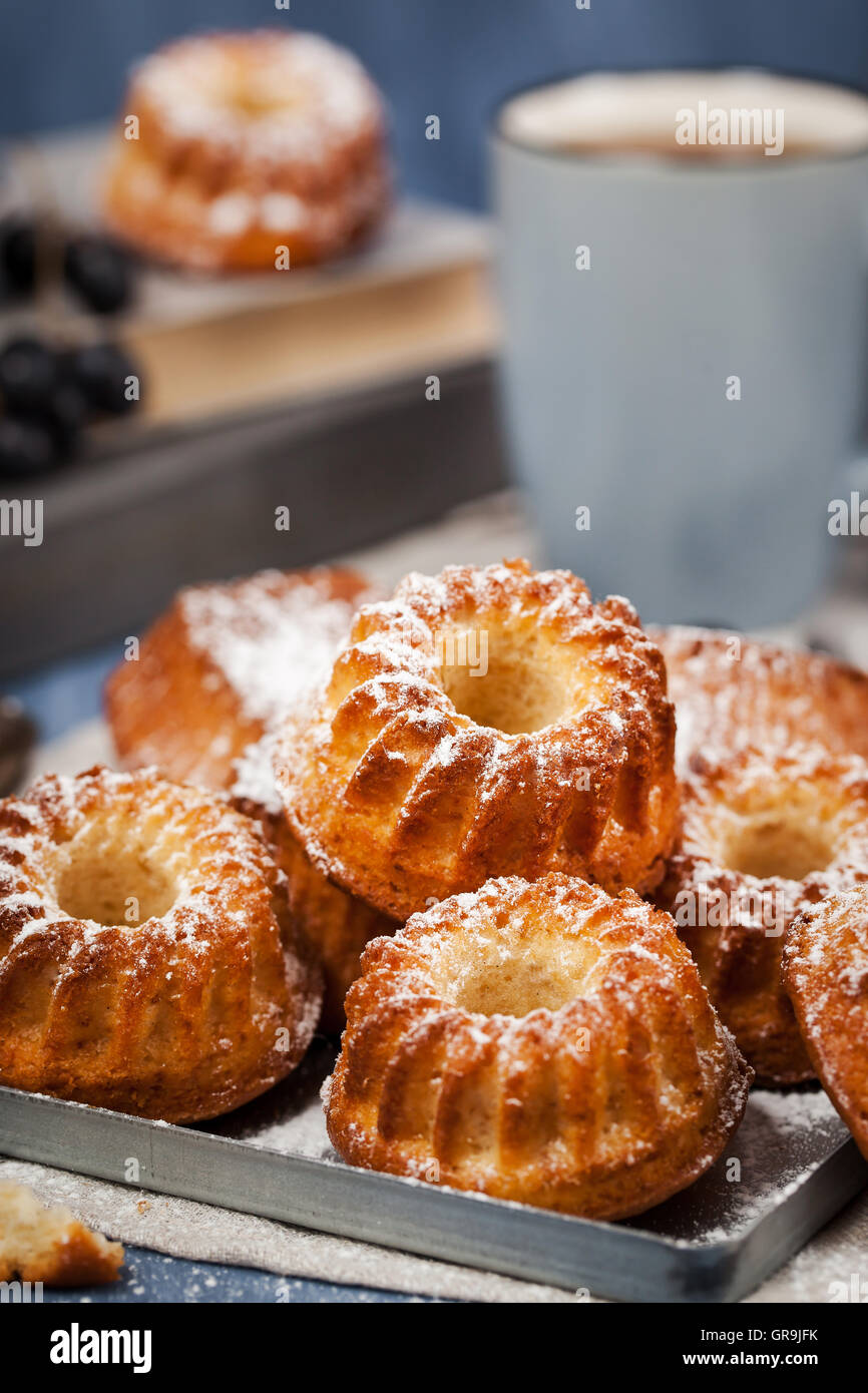Fresh homemade delicious mini bundt cakes (muffins) and cup of coffee on background - Stock Image