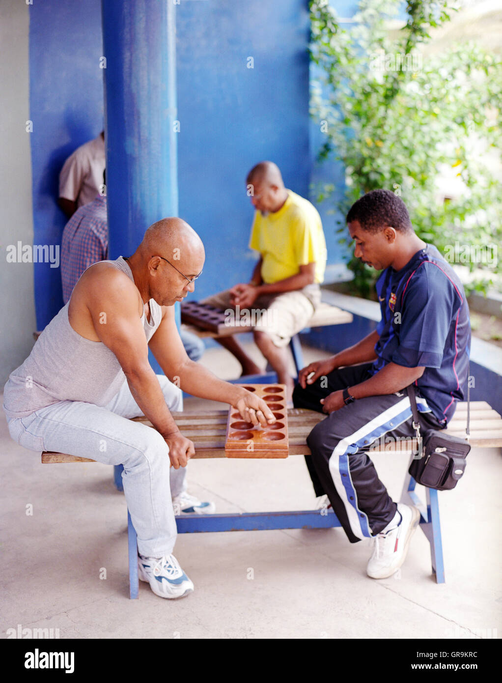 Local men play ouril int the city of Mindelo. Cape Verde, Africa.  Ouril is an abstract strategy game and is the - Stock Image