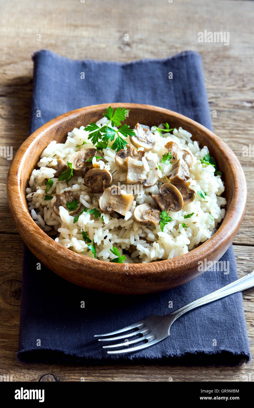 Mushroom risotto with parsley in wooden bowl - Stock Image