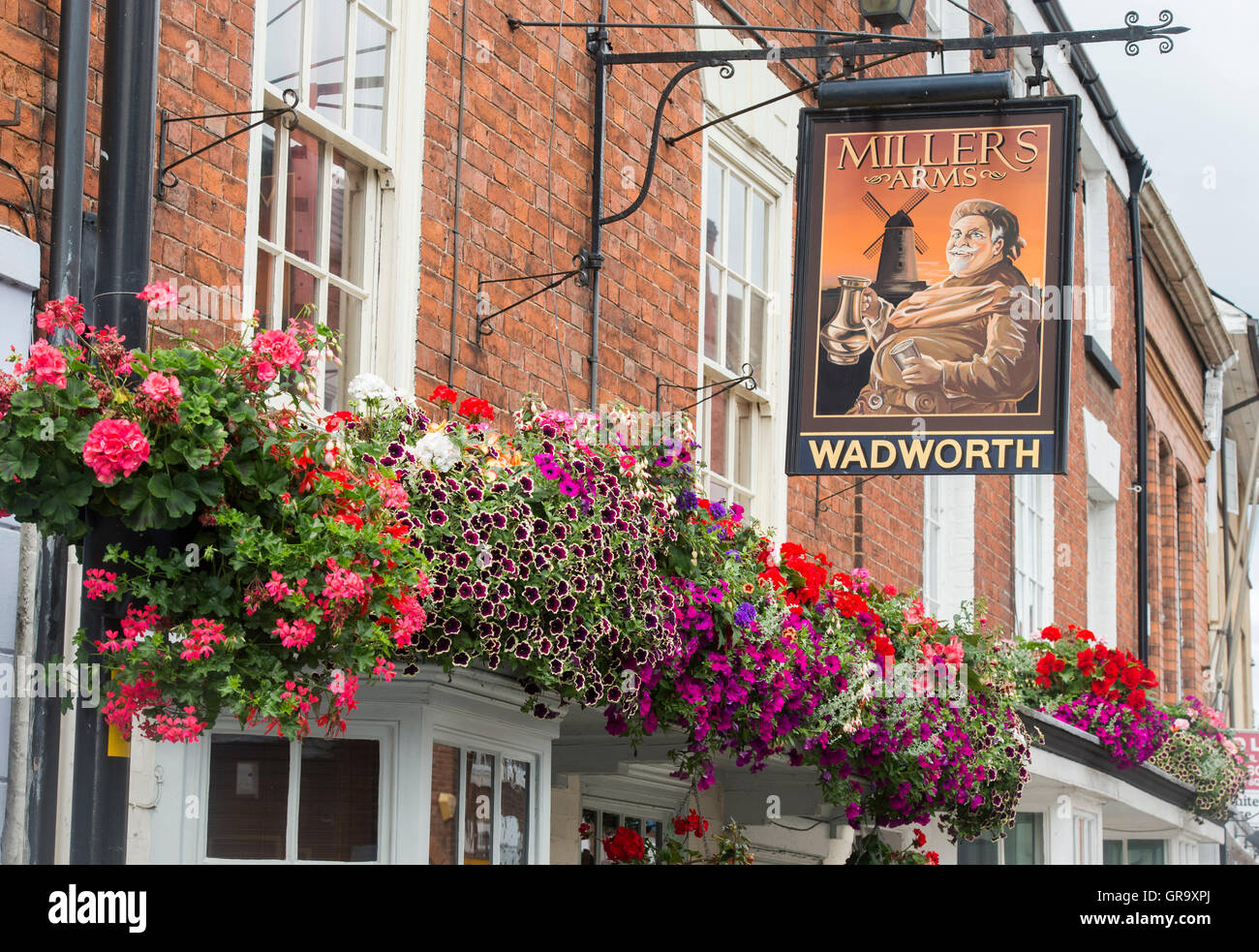 Hanging baskets of flowers on Millars arms pub in the town of Pershore, Worcestershire, UK - Stock Image