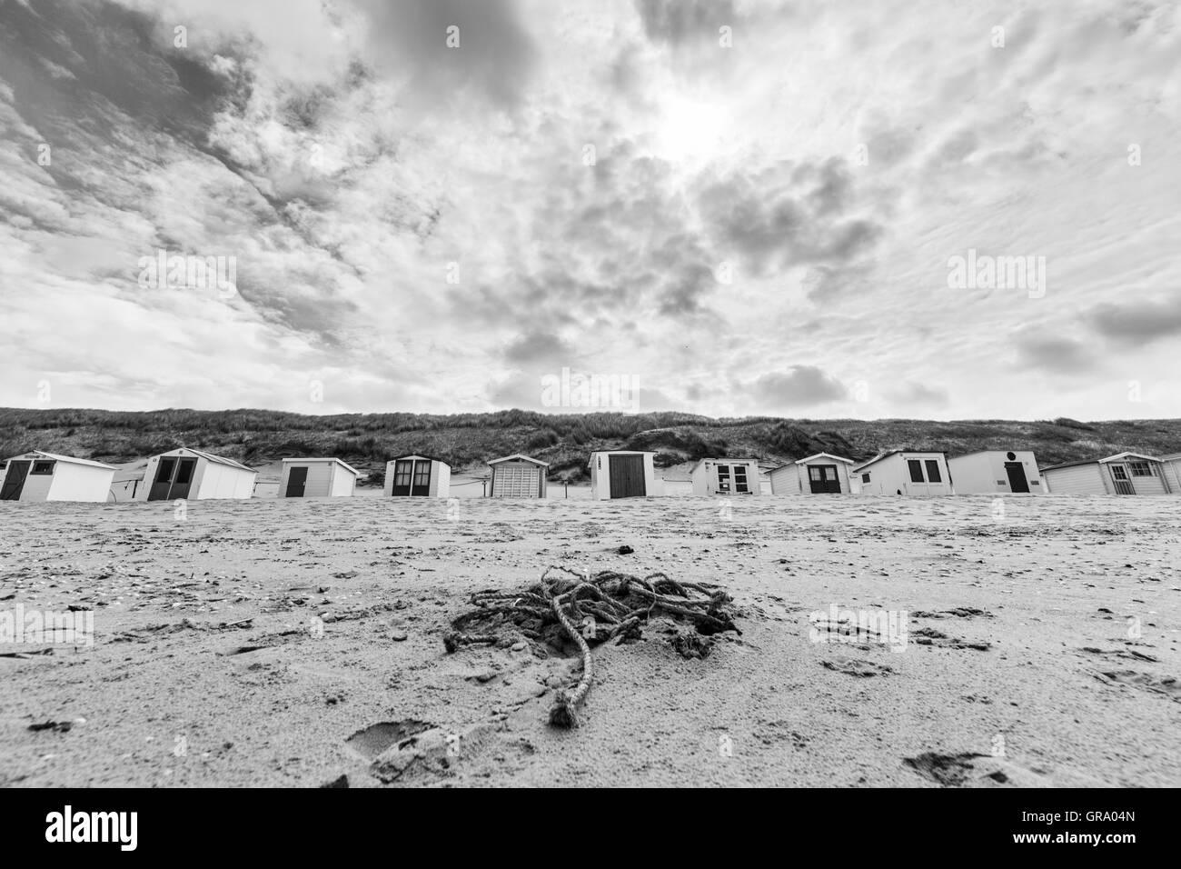 Blacj And White Photo Of A Netherland Beach With Dramatic Clouds And Small Bathing Huts - Stock Image