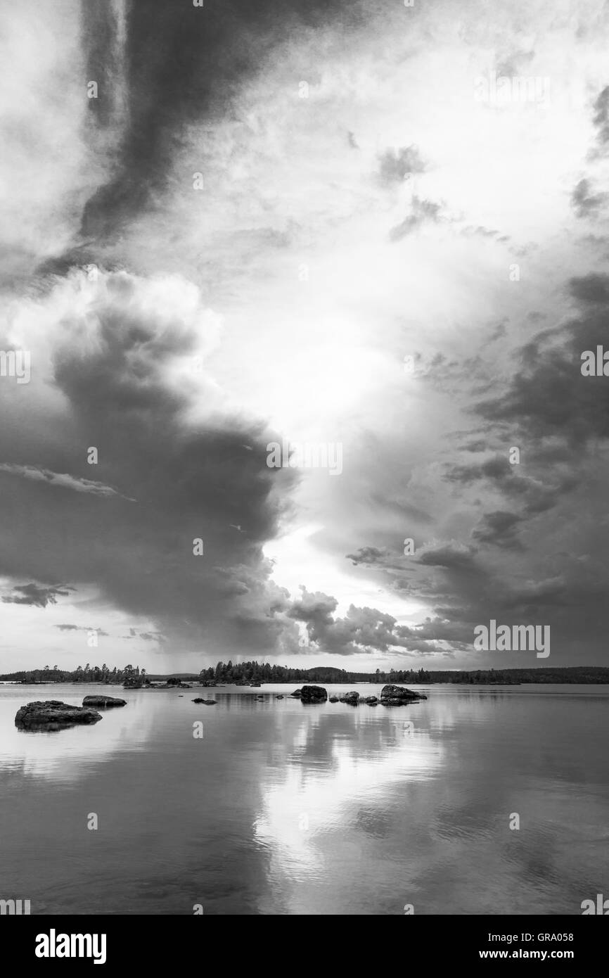 Black And White Photo Of The Reflections Of Dramatic Clouds In The Northern Finnish Lake Inari In Lapland - Stock Image