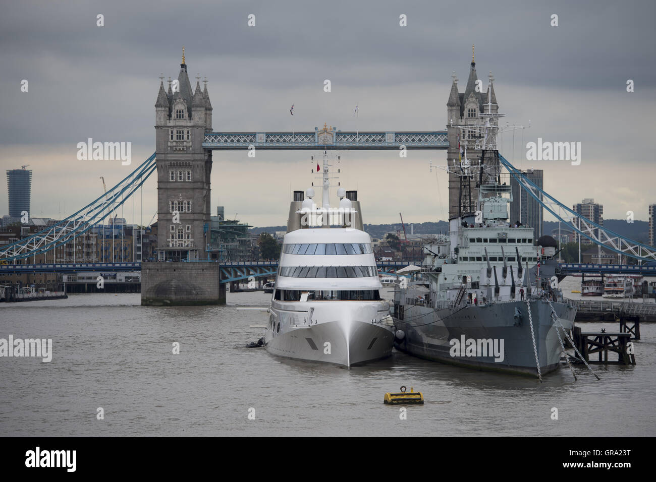 A 390ft motor yacht belonging to Russian tycoon Andrey Melnichenko, alongside HMS Belfast (right) on the River Thames - Stock Image