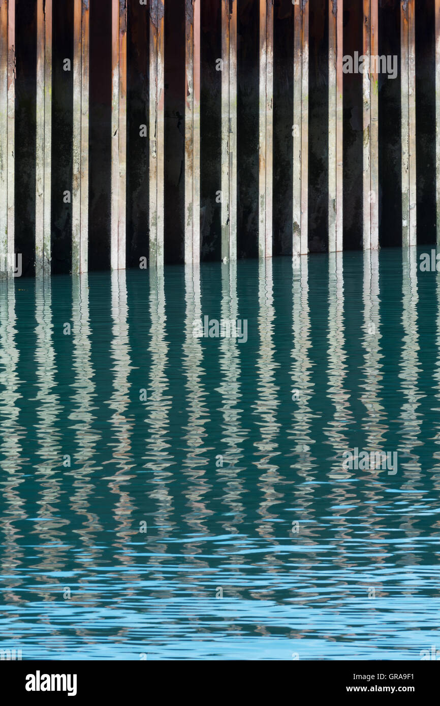 A rusting steel seawall is reflected in slightly rippled blue green water. - Stock Image