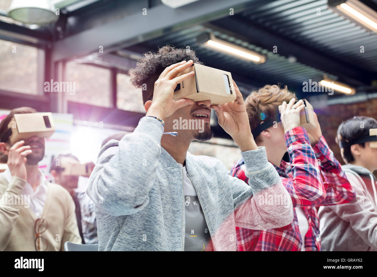 Audience trying virtual reality simulator glasses at technology conference - Stock Image